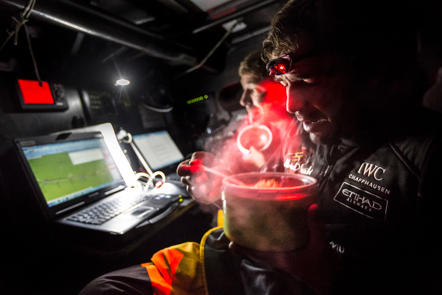 "March 28, 2015. Leg 5 to Itajai onboard Abu Dhabi Ocean Racing. Day 11.  Roberto Bermudez, aka Chuny, enjoys a hot meal after his watch as Simon ""SiFi"" Fisher looks at the latest routing in the Azzam nav station. Matt Knighton / Abu Dhabi Ocean Racing / Volvo Ocean Race"
